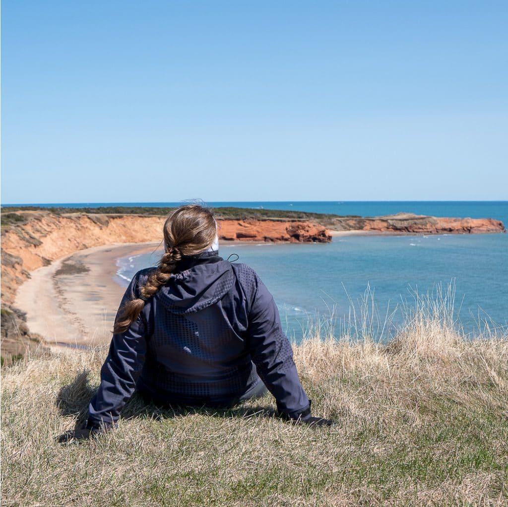 Jennifer sitting in front of the Magdalen Islands cliffs